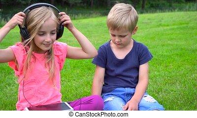 kids listen music on tablet outdoors - cute kids listen...