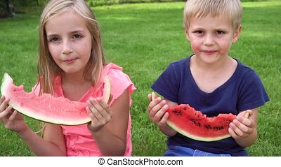 kids eating watermelon outdoors - two kids eating watermelon...