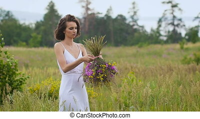 One young woman making a flower bunch standing on green...