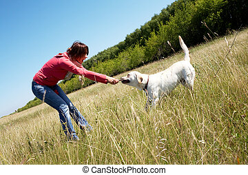 Play  - Photo of woman with her dog pulling branch