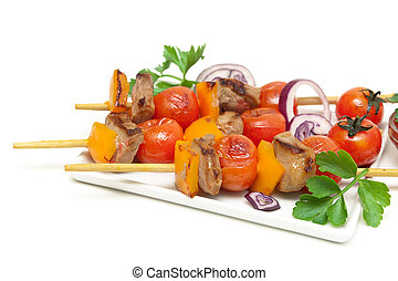 skewers of meat with vegetables on a plate close-up