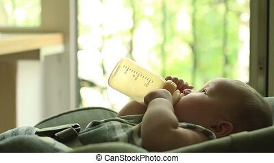 Baby eating milk from bottle HD