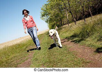 Walking  - Photo of girl and labrador walking on the road