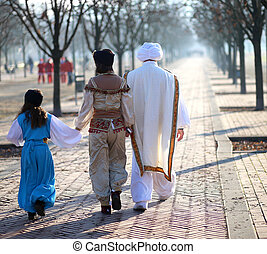 family with oriental clothes walking in the park - family...