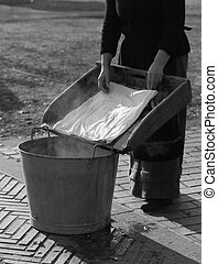 woman does the laundry in an old vat - older woman does the...