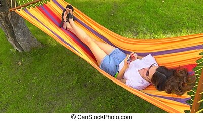 Slender pretty brunette laying in bright hammock and using...