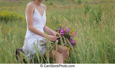 One young woman sitting on green field with flower bunch and...