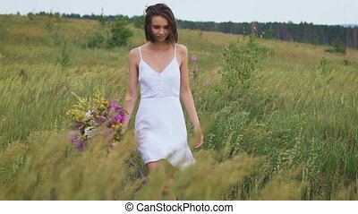 One young woman walking on green field enjoying a flower...