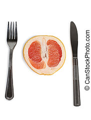 Grapefruit with fork and knife on a white background