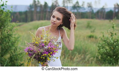 One young woman standing and youhing her hair on green field...