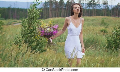 One young woman standing on green field with flower bunch