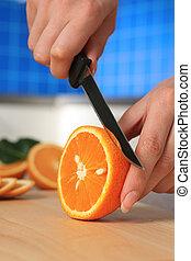 Female chopping juicy orange on the kitchen.