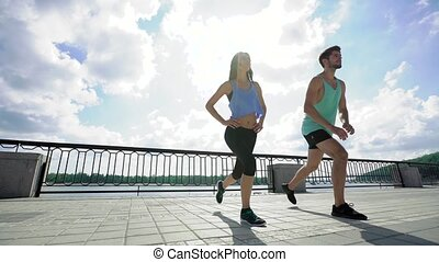 View from below of smiling couple in sportswear stretching outdoors at city bridge
