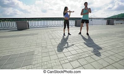 Attractive people working out on the bridge, warm-up and stretching of the arms and shoulders