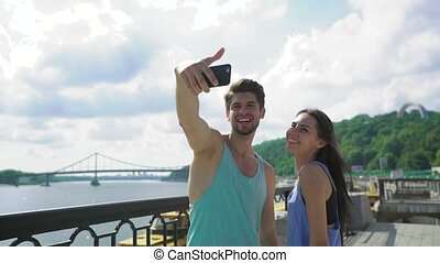 Selfie - Happy sporty couple taking self portrait photo at...