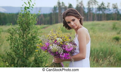 One young woman standing on green field with flower bunch -...
