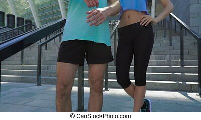 Close-up portrait of confident fit young couple standing with arms crossed looking at camera, stadium stairs as background