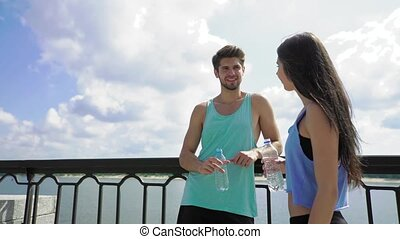 Couple staying hydrated with bottles of water relaxing after workout outdoors with happy facial expression