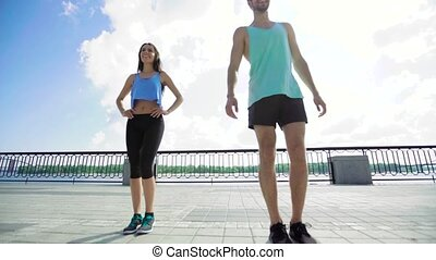 Full length of young couple exercising, personal trainer man...