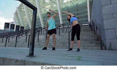 Healthy fitness woman and handsome sporty man on stadium...