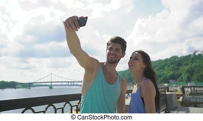Good looking young couple taking a selfie with a smartphone before working out together at city bridge