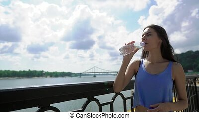 Attractive young brunette woman taking a water break while standing at bridge, looking at river landscape