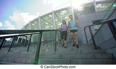 Fitness, sport, exercising and lifestyle concept - smiling couple in colorful sportswear running downstairs on stadium