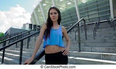 Motivated female athlete looking at camera standing near...
