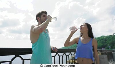 Friendship and lifestyle concept - smiling sporty couple having a break with bottles of water at city bridge, river as background
