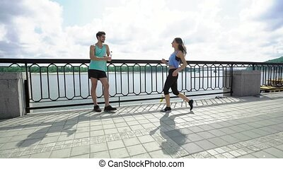 Tired young handsome man resting with bottle of water while smiling woman jogging to him across the bridge in the city