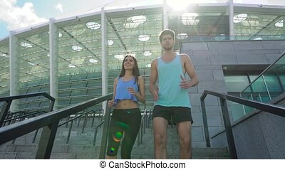 Close-up of athletic man and woman jogging down stairs together at modern stadium