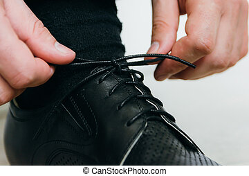 man ties the laces on his black shoes