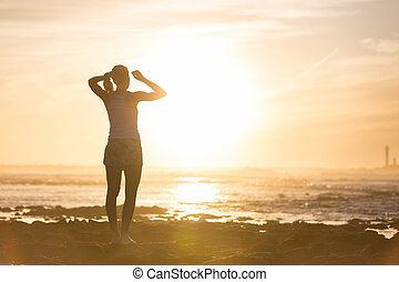 Woman on sandy beach watching sunset. - Silhouette of sporty...