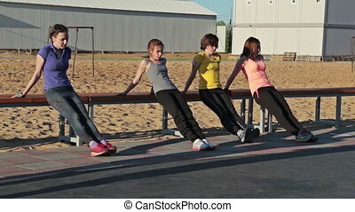 Girls doing push-ups on bench in park, crossfit