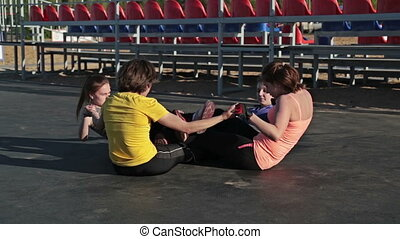 Young girls doing sit-ups exercising together, crossfit