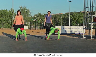 Group of people doing wheelbarrow exercise on workout
