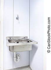sink on the wall - in an public restroom hangs on an wall of...
