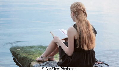 Pretty girl reading book outdoor - Red-haired girl reading...