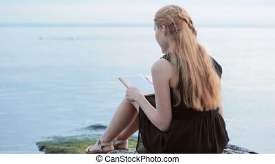 Alone red-haired girl reading book at river - back view of...