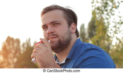 Thoughtful man smoking cigarette at sunset - Close-up of...