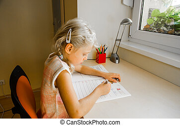 child doing homework - lovely little blond girl sitting at...