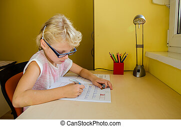child doing homework - lovely little blond girl with glasses...