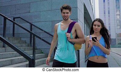 Charming sporty woman checking smartphone while walking with her boyfriend after exercising outdoors