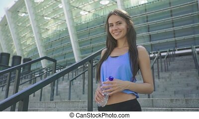 Cheerful young brunette woman athlete with bottle of water standing and smiling on stairs