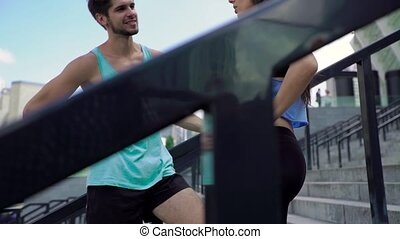 Charming woman and handsome man talking at stairs, relax after training, view from below
