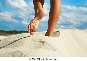 Barefoot - Close-up of woman going barefoot over sandy beach...