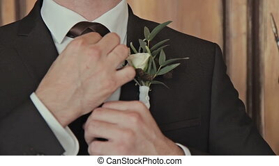 Groom corrects a tie - Groom with boutonniere corrects a tie...