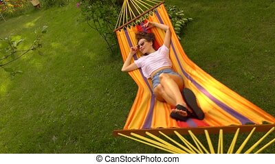 Happy brunette girl swaying in orange hammock 4K shot - Slim...