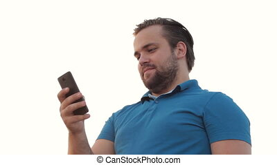 Smiling bearded man using phone - Low perspective of...