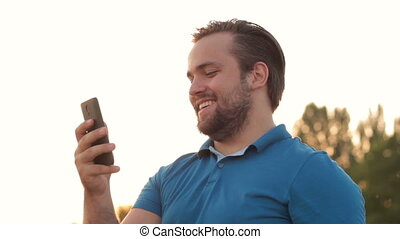 Smiling bearded man making videophone via cell - Side view...